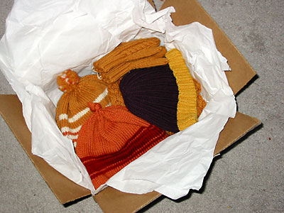 Sweater, hats, and mittens being packed for Afghans for Afghans